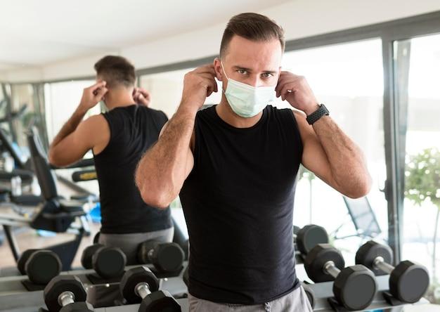 Hombre poniéndose máscara médica en el gimnasio
