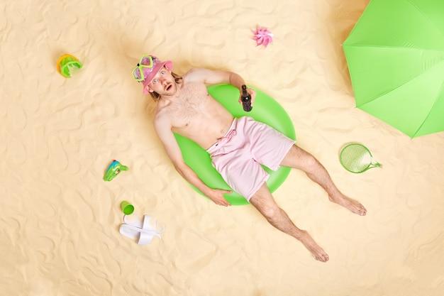 El hombre posa en el anillo de natación junto al mar rodeado de accesorios de playa, bebidas, cerveza, viste sombrero para el sol, máscara de snorkel y pantalones cortos se broncea en la luz del sol