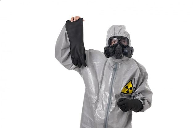 Un hombre posa con un traje gris, con una máscara de gas, posando sobre el fondo blanco.