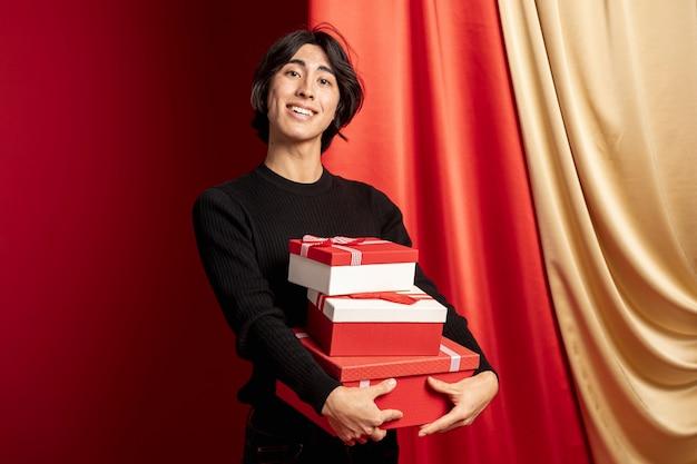 Hombre posando con cajas de regalo para año nuevo chino