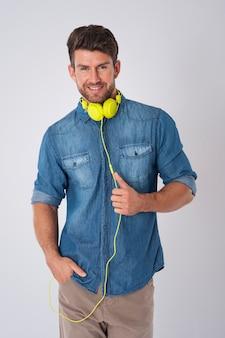 Hombre posando con camisa vaquera y auriculares