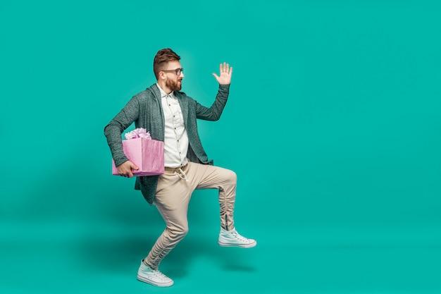 Hombre posando cómicamente con caja de regalo