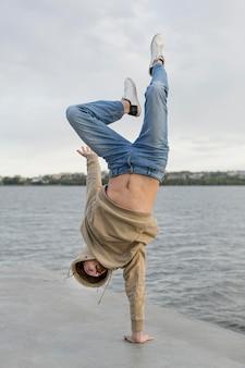 Hombre posando mientras está parado en una mano junto al lago