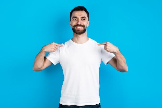 Hombre posando mientras se señala a sí mismo