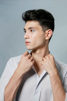 Hombre posando mientras sostiene el cuello de la camisa