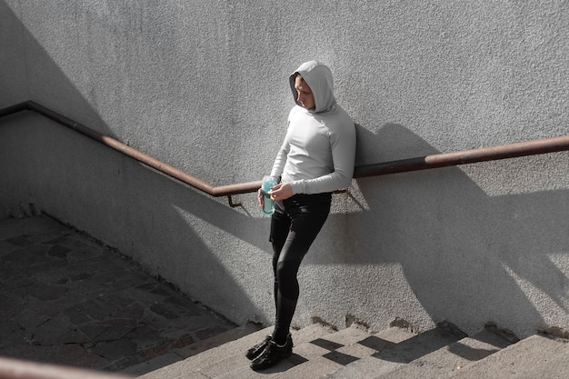 Hombre posando moda en escaleras con una botella de agua