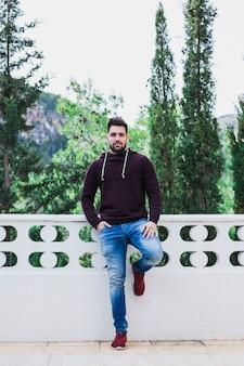 Hombre posando en la terraza cerca del bosque
