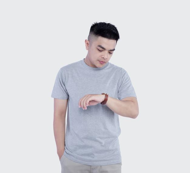 Hombre posando vistiendo camiseta gris mirando reloj en blanco
