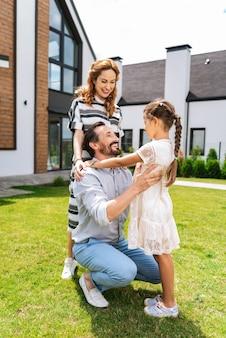 Hombre positivo alegre sonriendo mientras mira a su hija