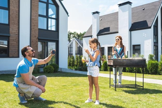 Hombre positivo alegre sosteniendo un teléfono inteligente mientras toma una foto de su hija