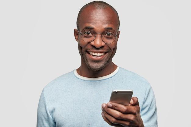 Hombre positivo con amplia sonrisa, sostiene un teléfono celular moderno, escribe mensajes de texto y comentarios, navega por las redes sociales