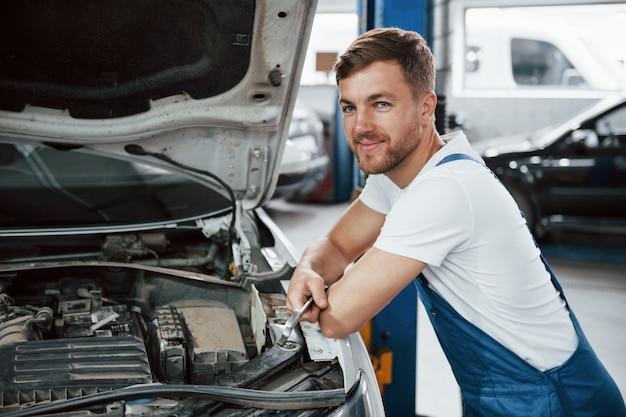 Hombre positivo apoyado en el coche. empleado con uniforme de color azul trabaja en el salón del automóvil.