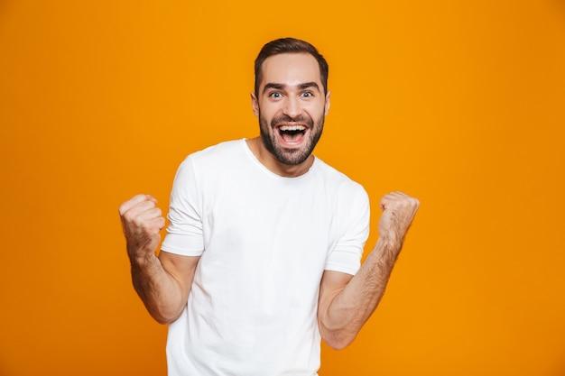 Hombre positivo con barba y bigote apretando los puños de alegría mientras está de pie, aislado en amarillo