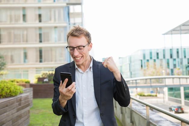 Hombre positivo emocionado recibiendo mensaje