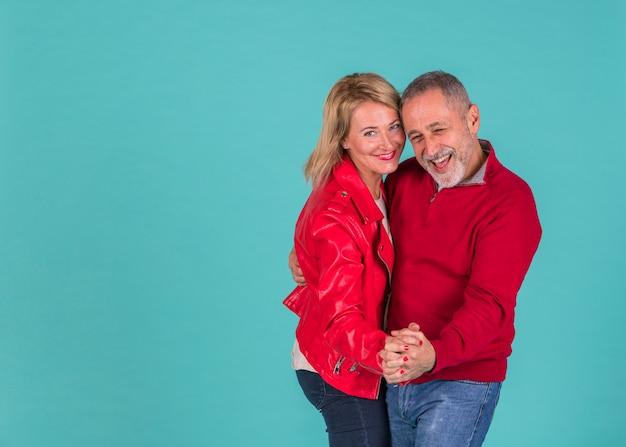 Hombre positivo envejecido bailando con mujer riendo