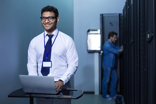 Hombre positivo inteligente alegre de pie frente a la computadora portátil y sonriendo mientras trabaja en ella