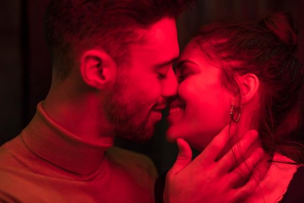 Hombre positivo joven que besa a la mujer sonriente en rojez