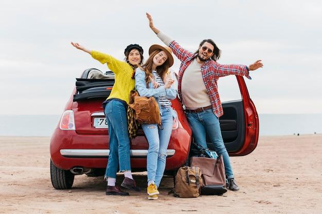 Hombre positivo con las manos levantadas cerca de abrazar a las mujeres y el coche en la playa del mar