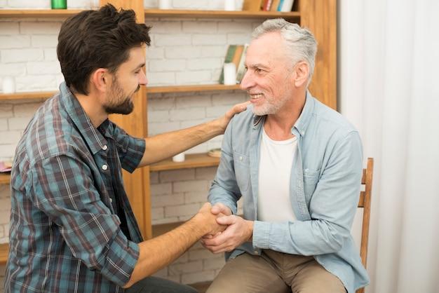 Hombre positivo mayor que sacude las manos con el individuo feliz joven en sitio