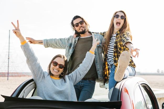 Hombre positivo y mujeres lloronas divirtiéndose e inclinándose fuera del auto