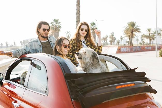 El hombre positivo y las mujeres sonrientes acercan al perro que se inclina hacia fuera del auto