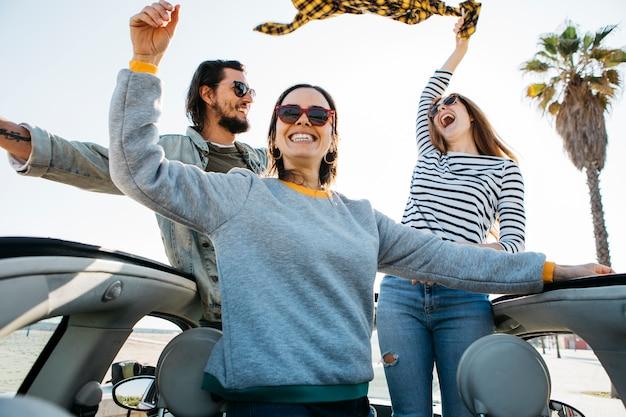 Hombre positivo y mujeres sonrientes divirtiéndose e inclinándose fuera del auto