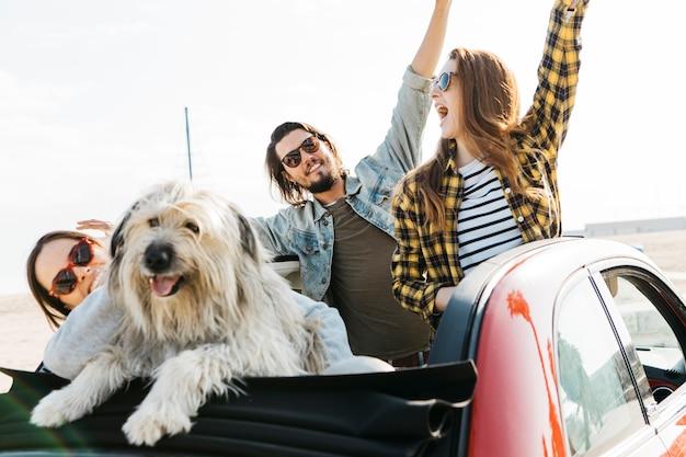 El hombre positivo y las mujeres sonrientes con las manos levantadas acercan al perro que se inclina hacia fuera del auto