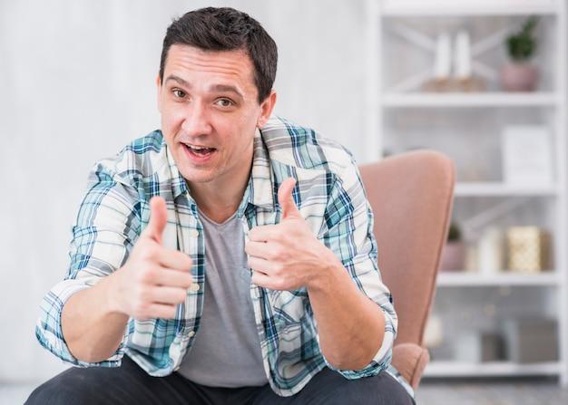 Hombre positivo que muestra los pulgares para arriba en silla en casa
