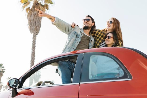Hombre positivo que señala cerca de mujeres sonrientes que se inclinan hacia fuera de auto