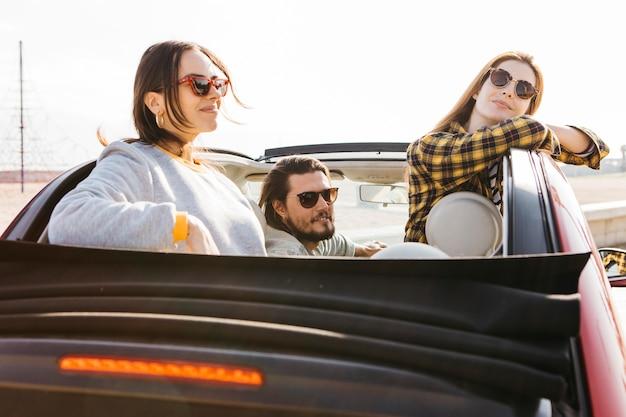 Hombre positivo que se sienta en coche cerca de mujeres sonrientes que se inclinan hacia fuera del auto