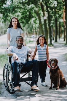 Hombre positivo en silla de ruedas mujer joven y niña
