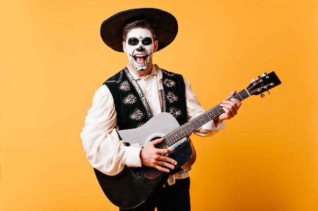 Hombre positivo en sombrero canta serenata. chico activo con guitarra en sus manos posando en la pared amarilla.