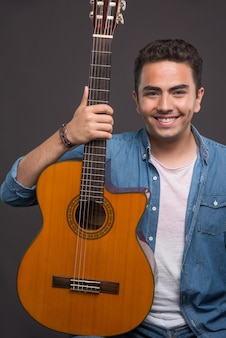 Hombre positivo sosteniendo una hermosa guitarra sobre fondo negro. foto de alta calidad