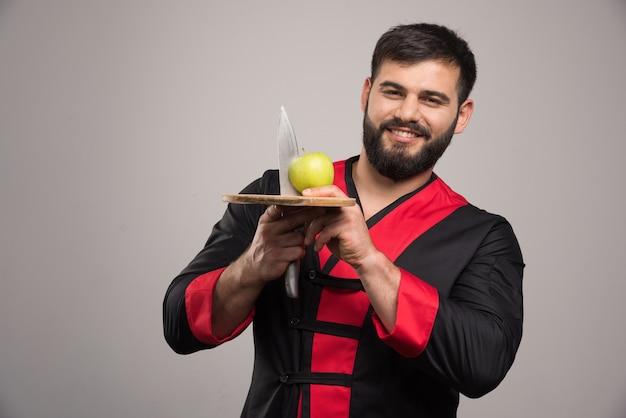 Hombre positivo sosteniendo una manzana con un cuchillo sobre tabla de madera.
