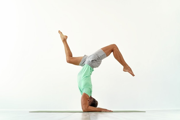 Hombre practicando equilibrio pose de yoga en estudio blanco