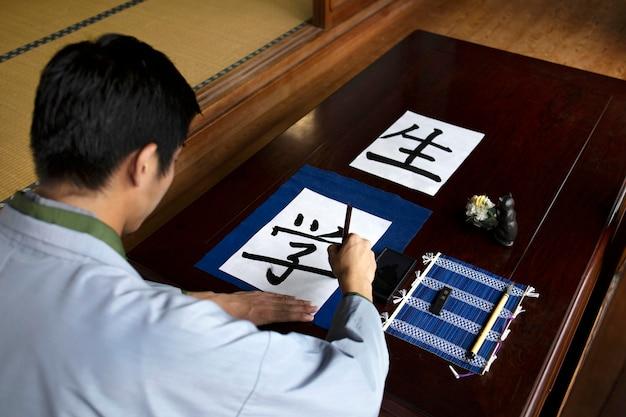 Hombre practicando la escritura japonesa con una variedad de herramientas