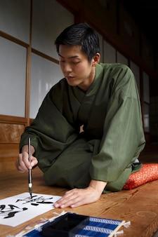 Hombre practicando la escritura japonesa