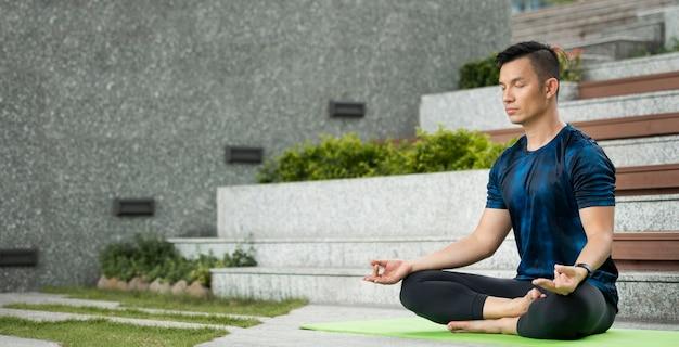 Hombre practicando yoga al aire libre con espacio de copia
