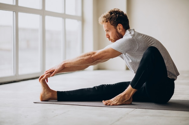 Hombre practicando yoga en la colchoneta en casa