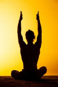 El hombre practicando yoga en la luz del atardecer