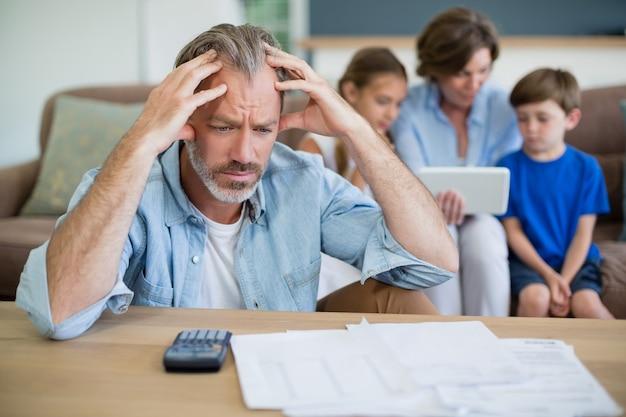 Hombre preocupado calculando facturas en la sala de estar