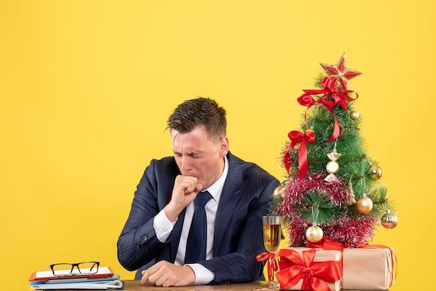 Hombre preocupado cerrando los ojos sentado en la mesa cerca del árbol de navidad y presenta en amarillo