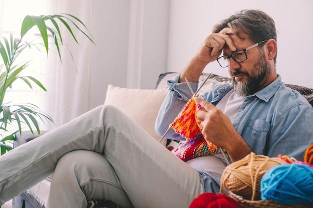 Hombre preocupado comprobar su trabajo de punto en casa sentado y relajado en el sofá. actividad de hobby de tejer y personas caucásicas masculinas que buscan y aprenden a hacer
