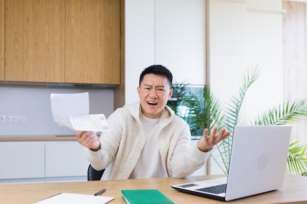 Hombre preocupado y estresado calculando facturas, gastos de impuestos y contando las finanzas del hogar