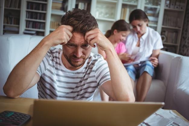 Hombre preocupado sentado en la mesa con facturas y laptop