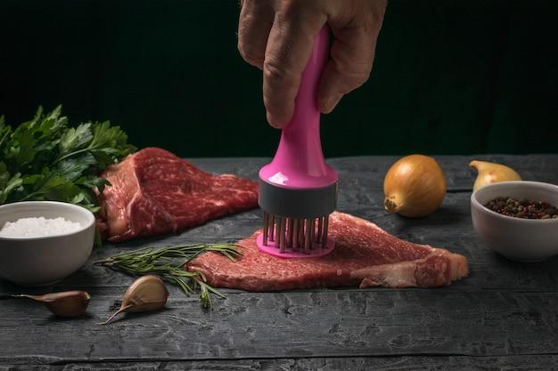 Un hombre prepara un filete de ternera con un dispositivo especial. cocinar platos de carne.