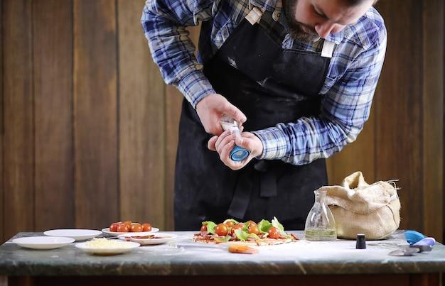 Un hombre prepara una pizza, amasa la masa y pone los ingredientes.