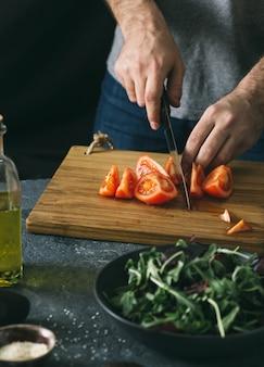 Hombre preparando ensalada de verduras