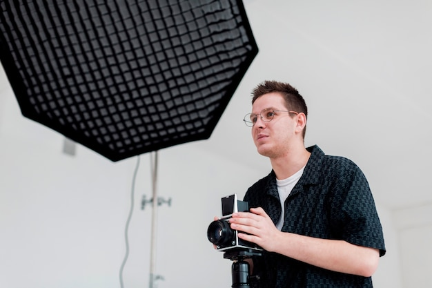 Hombre preparando el estudio para un rodaje y mirando a otro lado