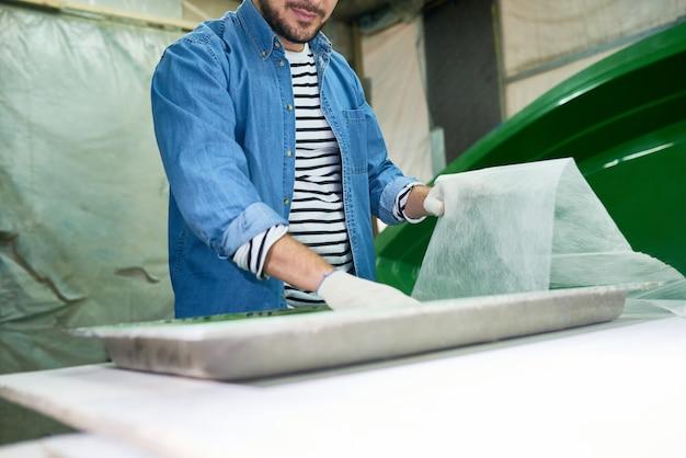 Hombre preparando herramientas de pintura en taller